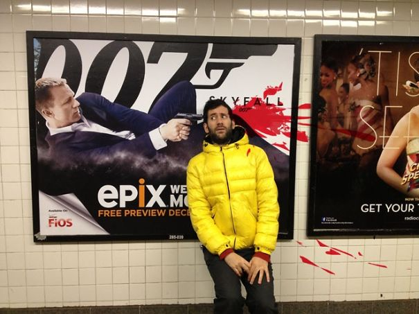 Artist Poses Next To Movie Ads To Raise Awareness Of Violent Imagery In Public Spaces