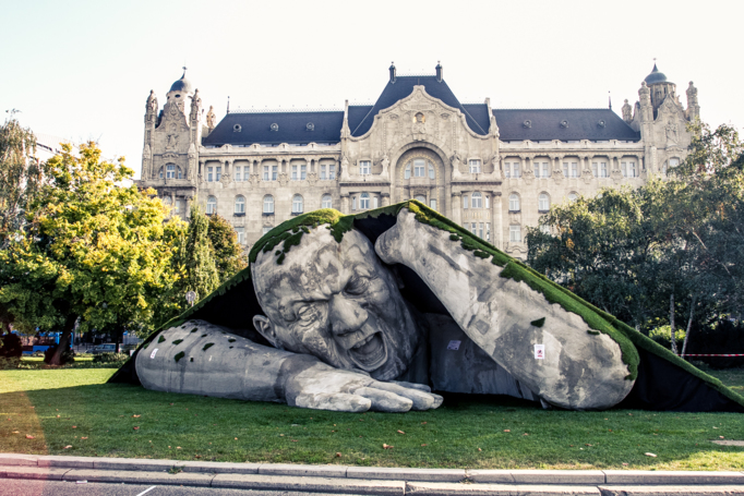 A Massive Outdoor Sculpture of a Man Bursting From the Ground in a Public Square