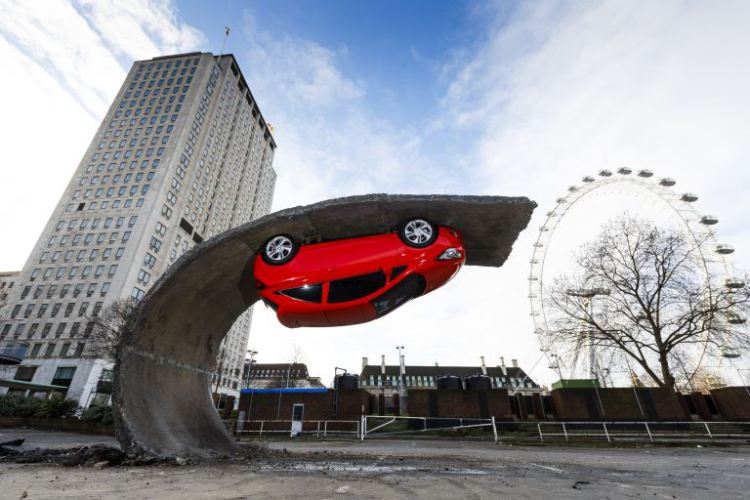 An Art Installation Featuring an Actual Car Parked Upside Down on a Curved Piece of Asphalt