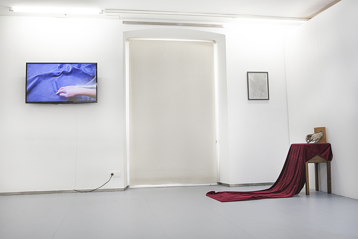 Exhibition view. From left to right: Nona Inescu, Where touch begins, we are, 2016, single channel HD video, sound: Chlorys / voiceover text by Anne Carson; Emilio Rojas, History of European Morals, 2017, installation with table, velvet, old book, sculpture with dandelions seeds and resin. Photo credit: Javier Lamela