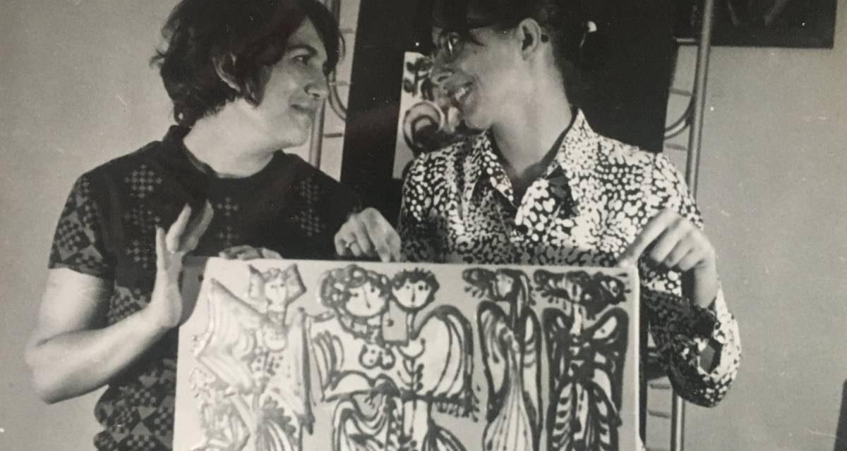 Florentina Mihai și Ligia Dumitrescu ținând o placa ceramică pictată cu o scenă din viața rurală